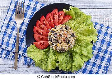 Rice with mushrooms and green lettuce leaves on rustic table background