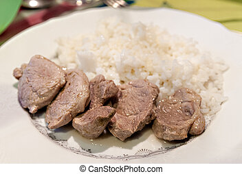 rice with pieces of meat on a plate