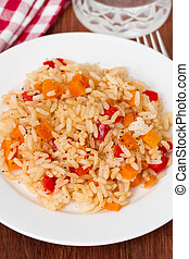 rice with vegetables on plate and glass of water