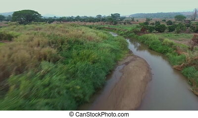 Rich and vibrant farm by a river - A high angle shot of a...