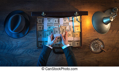 Vintage rich businessman's desk with a briefcase filled with dollar packs, he is counting paper currency