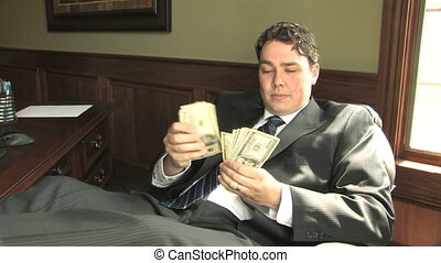 A businessman in a suit counts hundred dollar bills at his office desk