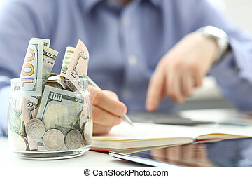 Rich jar full or US banknotes and coins with businessman arms in background counting expenses with his cellphone