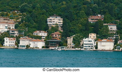 A rich luxury quarter of residential buildings on green hills on the seashore that are surrounded by greenery. View from a passing boat, Istanbul, Turkey