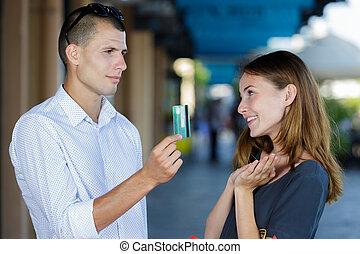 rich man is giving woman debit card