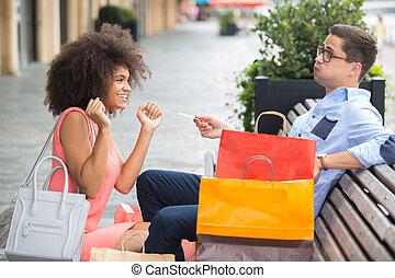 rich man is giving woman debit card to shopaholic wife