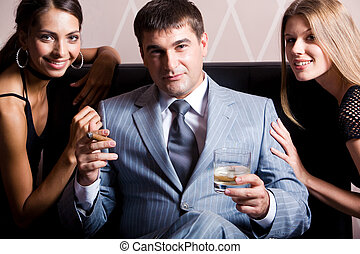 Portrait of handsome man in grey suit sitting with whisky and cigar between two pretty women in casino
