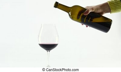 Rich red wine being poured into balloon wineglass, white, slowmotion