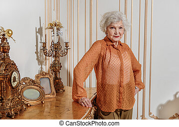 Rich senior lady is proud of her gorgeous apartment