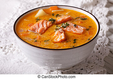 Rich soup with salmon, vegetables and thyme close-up
