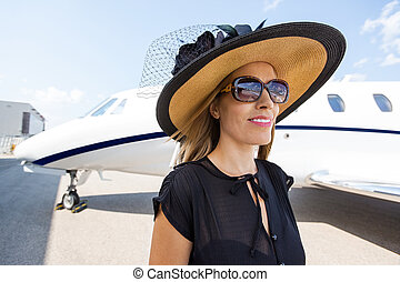 Rich Woman Standing Against Private Jet