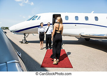 Rear view of rich woman walking towards private jet while pilot and stewardess standing at airport terminal