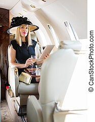 Rich Woman With Drink Using Digital Tablet In Private Jet