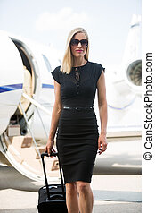 Rich Woman With Luggage Walking Against Private Jet
