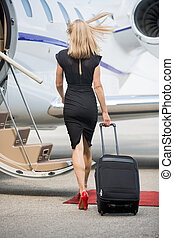 Full length rear view of rich woman with luggage walking towards private jet at airport terminal