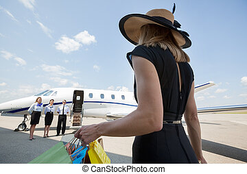 Rich Woman With Shopping Bags Walking Towards Private Jet