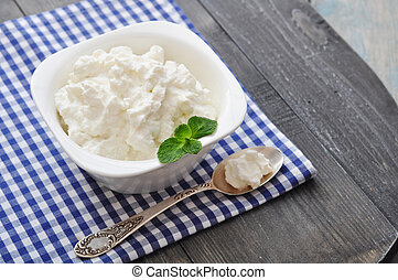 Ricotta cheese in bowl with mint on wooden background