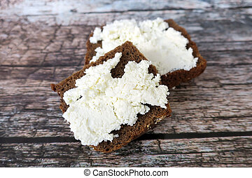 Ricotta on brown bread on wooden background