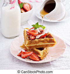 Ricotta waffles served with fresh strawberries and maple syrup
