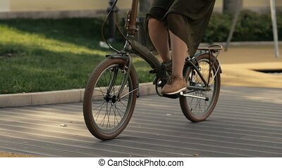 Ridding bicycle wheels. Close up young woman bicycle riding...