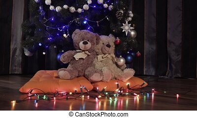Ride a camera on two toy teddy bears sitting on orange pillows near a Christmas decoration tree. Christmas decor, apartment, soft toys, luminous garlands