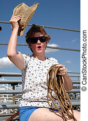 A woman holding a coil of rope and waving a cowboy hat on the bleachers