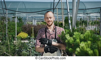 Ride the camera. The bearded gardener looks and smiles at the camera. A sunny day in agricultural greenhouse. Portrait of a man who works in the garden.