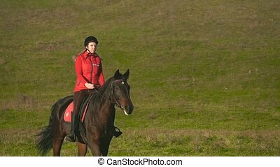 Rider galloping on a green field on horseback. Slow motion