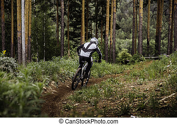 rider on a bicycle coming down mountain