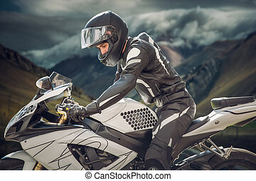 Rider on a motorcycle with Chief Mountain as the background. mountains of a cloud