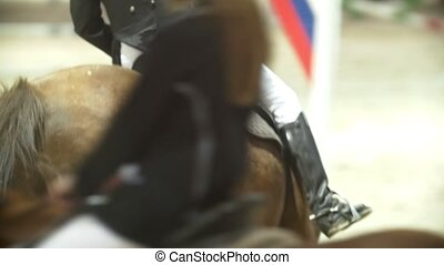 Rider on black horse galloping at show jumping competition,...