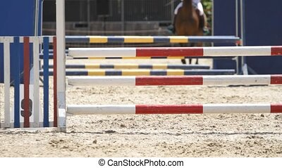 Rider on horse jumps over barriers at competitions