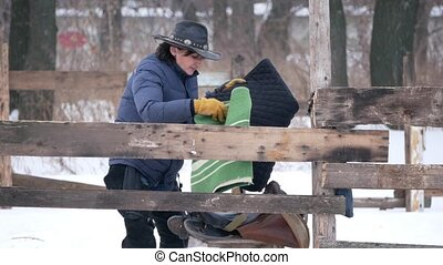 Rider on the farm prepares the saddle before the riding,...