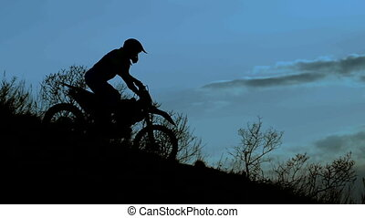 Rider silhouette in the night. He goes down the hill on his extreme motocross bike.