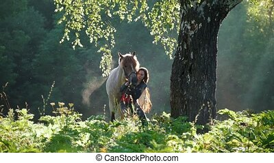 Rider straightens the headband of a horse in the woods early...