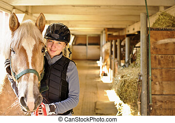 Young female rider with horse inside stable