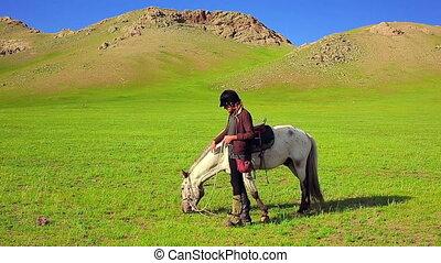 Rider Woman with mongolian horse at steppe near Terkhiin...