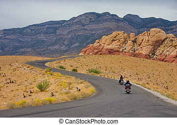 Motorcyclists riding along a curving road in the desert toward distant mountains