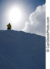 Ridgeline - A man stands atop a snowy mountain ridge with...