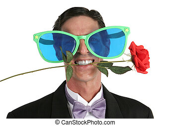 A man in a tuxedo with a rose in his mouth and oversized sunglasses