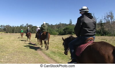 Riding a horse on a wide ranch - A tracking shot from behind...
