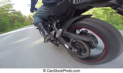 Riding a motorcycle, view on rear wheel