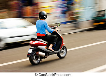 Riding a scooter - Panning shot of a young girl riding a...
