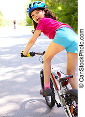 Riding away - Rear view of a little girl on bike looking at...