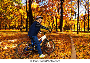 Riding bicycle in the autumn park