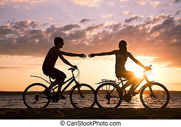 Riding bicycles - Silhouettes of happy couple stretching...