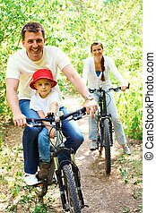 Riding bicycles - Portrait of happy man with son riding a ...