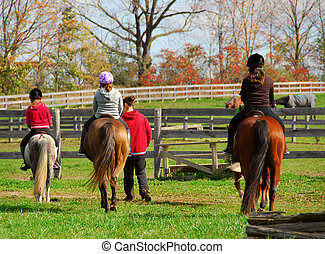 Riding - Children riding ponies and horses in a countryside