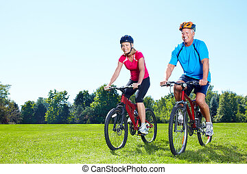Riding couple. - Happy senior couple  riding  in the park.