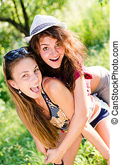 riding fun: portrait of 2 beautiful brunette young women best friends having joyful time laughing & looking at camera on green summer outdoors copy space background